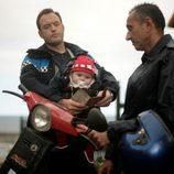 Alfredo revisa la documentación con un bebé en brazos