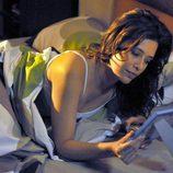 Jimena mira una foto en la cama