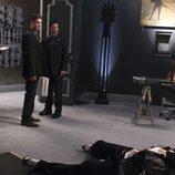 Un hombre yace muerto ante la mirada de Taylor y Flack