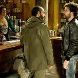 Raúl habla con un hombre bajo la atenta mirada de Carola