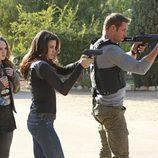 Meghan Ory y Josh Holloway apuntando con la pistola en 'Intelligence'