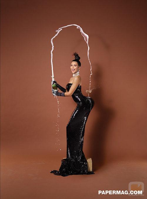 Kim Kardashian sostiene una copa con su trasero mientras descorcha una botella de champán