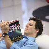 El actor Eric Mabius lee tumbado en 'Ugly Betty'