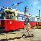 Edurne subida en un patinete, frente a un tranvía, en la ciudad de Viena