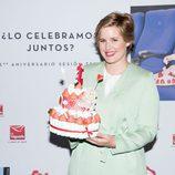 Tania Llasera sostiene sonriente una tarta de golosinas