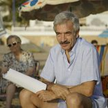 Imanol Arias sujeta un papel mientras se está rodando en la playa 'Cuéntame cómo pasó' en Benidorm