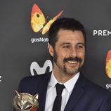 Hugo Silva sonriente con su galardón en la alfombra roja de los Premios Feroz 2017