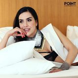 Roko tumbada sobre la cama, con un collar enorme y chaleco blanco para Point Magazine