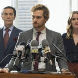 Daniel Rand (Finn Jones), Ward Meachum (Tom Pelphrey) y Joy Menchum (Jessica Stroup) durante una rueda de prensa en 'Iron Fist'