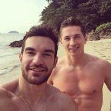 James Longman posa sin camiseta junto a un amigo en la playa