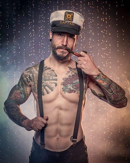 Daniel G. Prim, semidesnudo, con tirantes y una gorra de marinero