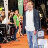 Pose de Juan Gea, actor del 'Ministerio del Tiempo', sonriendo en la alfombra naranja del FesTVal