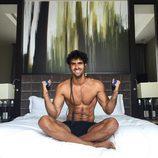 Juan Betancourt sonríe semidesnudo en la cama