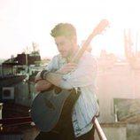 Luis Cepeda abraza una guitarra en una de las imágenes promocionales de su single
