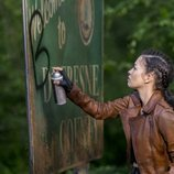 Rosita escribe encima del cartel de un pueblo en 'The Walking Dead'