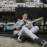 Alfred García posa con su guitarra eléctrica en una tienda de discos