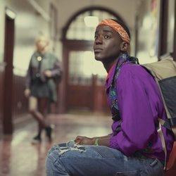 Ncuti Gatwa sentado en el pasillo en 'Sex Education'