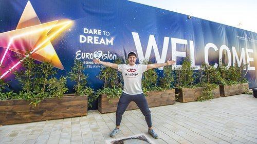 Miki, en Tel Aviv, frente a una enorme pancarta de bienvenida