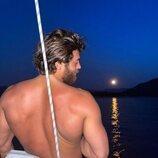 Can Yaman posa de espalda en un barco