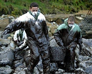 Dos jóvenes limpiando 'chapapote'